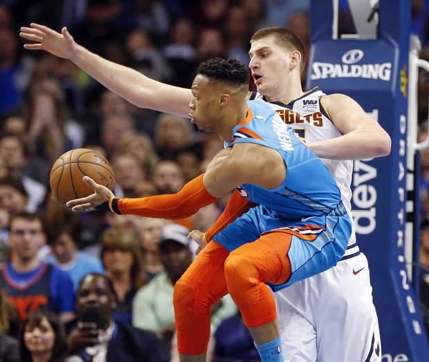 Oklahoma City's Russell Westbrook (0) passes away from Denver's Nikola Jokic (15) in the fourth during an NBA basketball game between the Denver Nuggets and the Oklahoma City Thunder at Chesapeake Energy Arena in Oklahoma City, Friday, March 29, 2019. Denver won 115-105. Photo by Nate Billings, The Oklahoman