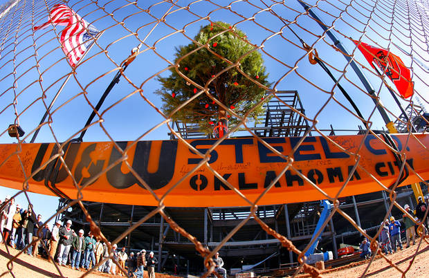 "Dec. 20, 2007: The beam that will complete the highest point of the expansion to the Oklahoma State University football stadium is hoisted with a Christmas tree mounted to it during the ""Topping off the Stadium"" ceremony at Boone Pickens Stadium. [Photo by Chris Landsberger, The Oklahoman Archives]"