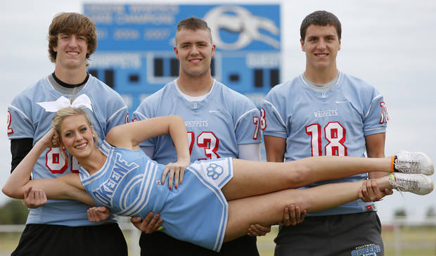 photo - Okeene quadruplets, from left, Mikey, Jamie and Scott Dobrinski hold their sister Shelby in Okeene, Wednesday October 16, 2013. Shelby is a cheerleader and her brothers play football. Photo By Steve Gooch, The Oklahoman