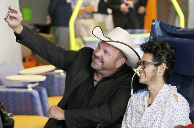 Garth Brooks takes a selfie with Jose Padilla, 16, during a visit by Brooks to The Zone at The Children's Hospital in Oklahoma City, Friday, July 14, 2017. Brooks and his foundation, Teammates for Kids, have created Child Life Zones across the country where patients, along with their families, can come to have fun, learn and get to be kids. Photo by Nate Billings, The Oklahoman