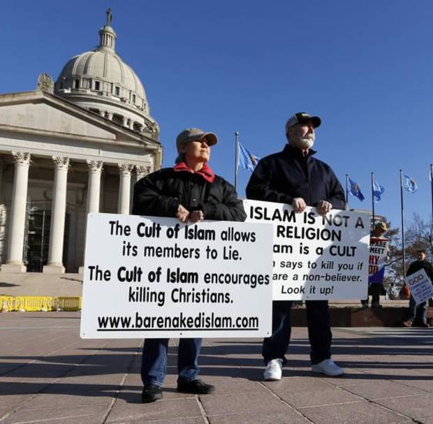 "Tempest and Ron Young, husband and wife from Moore, hold anti-Islamic signs as Oklahoma Muslims enter the State Capitol during the 2016 ""Muslim Day of the Capitol."" [Photo by Steve Sisney, The Oklahoman]"