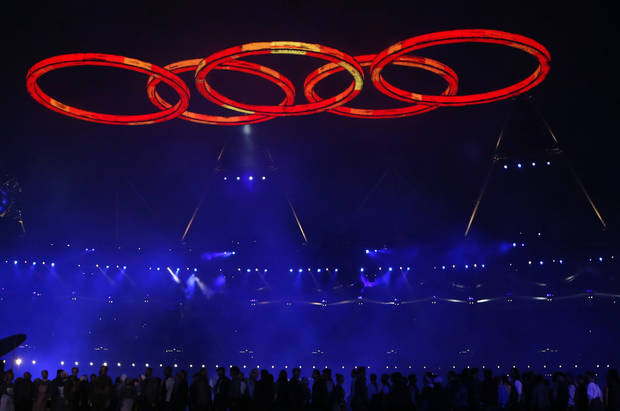 photo - Performers are silhouetted as the Olympic rings are illuminated during the Opening Ceremony at the 2012 Summer Olympics, Friday, July 27, 2012, in London. (AP Photo/Matt Dunham)
