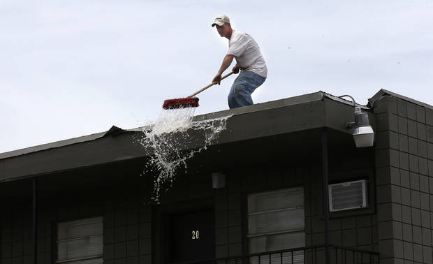 photo -  Jimmy Reynolds brushes water off the roof of the Oakwood Apartments, 5824 NW 34, on Friday. PHOTO BY SARAH PHIPPS, THE OKLAHOMAN   SARAH PHIPPS -