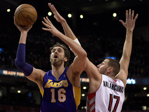 photo - Los Angeles Lakers center Pau Gasol (16) drives to the hoop past Toronto Raptors center Jonas Valanciunas during first-half NBA basketball game action in Toronto, Sunday, Jan. 19, 2014. (AP Photo/The Canadian Press, Frank Gunn)
