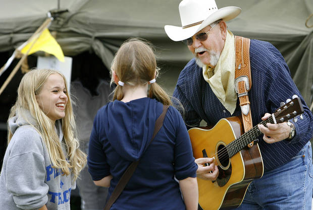 "photo - BRENNA NIXON: ""Cowboy Jim"" Garling strums his guitar, teaching Brenna (cq) Nixon and Jennifer Crow the art of yodeling at the Choctaw Land Run Festival in Choctaw Creek Park Thursday,  April 17, 2008. Both girls attend Piedmont Middle School.      BY JIM BECKEL, THE OKLAHOMAN ORG XMIT: KOD"
