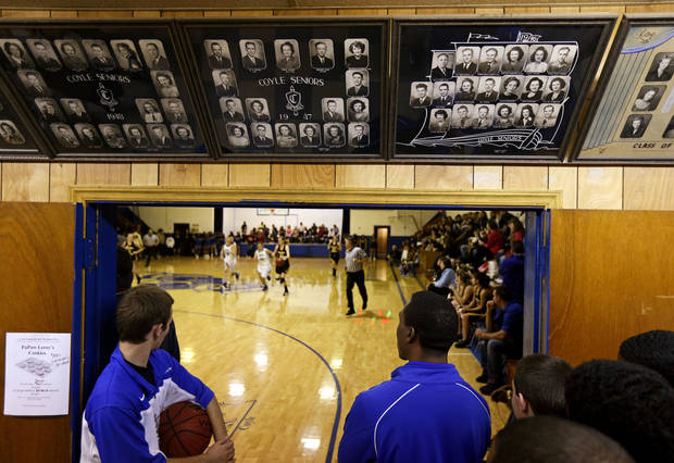 photo - Members of the Coyle boys basketball team stand under class photos near an entry to the gym before a game in Coyle, Okla., Tuesday, Jan. 22, 2013. Coyle High School hosted its final regular season basketball game in its current gym that was finished in 1939. Photo by Bryan Terry, The Oklahoman