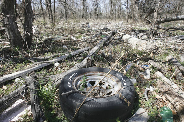 photo - A discarded tire is found among the 2-year-old trash that washed on shore when Arcadia Lake flooded. Equestrian trail riders are upset about the trash.  Photo by PAUL HELLSTERN, THE OKLAHOMAN