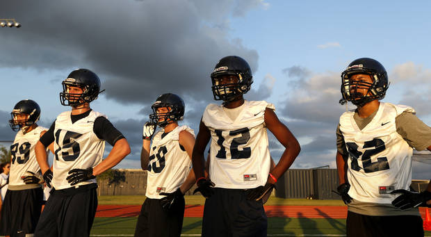 photo - Player line up during drills at the first football practice for Southmoore High School, Tuesda, Aug. 13, 2013, in Moore, Okla. Several of the players lost their homes in the May 20 tornado. Photo by Sarah Phipps, The Oklahoman