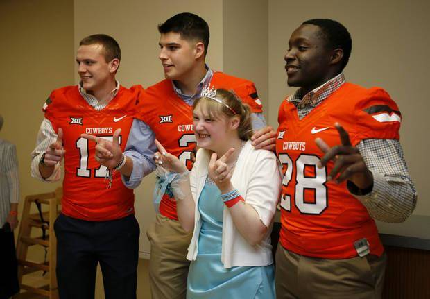 "Krystal Littler gets a photo with Oklahoma State University football players Austin Hays, left, Mason Rudolph and James Washington, at right, during ""Night to Shine,"" a prom-night experience for people with special needs, ages 16 and older held on Friday, Feb. 12, at Putnam City Baptist Church, in partnership with the Tim Tebow Foundation. [Photo by Bryan Terry, The Oklahoman]"