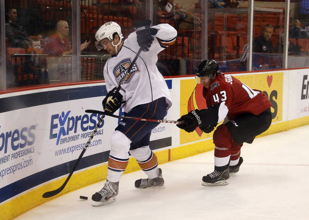 photo - Justin Schultz of the Oklahoma City Barons tries to keep the puck away from Mike Sgarbossa of the Lake Erie Monsters during AHL hockey game at the Cox Convention Center in Oklahoma City, Tuesday, October 23, 2012. Photo by Bryan Terry, The Oklahoman