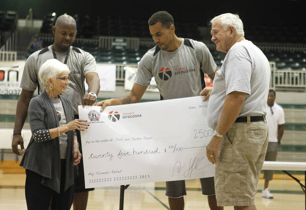 photo - Moore tornado victims Jackie and Dub Raper receive a donation from Alonzo Richmond, left, and Thabo Sefolosha during the 2nd Annual Thabo Sefolosha Basketball Clinic at Santa Fe High School in Edmond, OK, Saturday, September 14, 2013,  Photo by Paul Hellstern, The Oklahoman