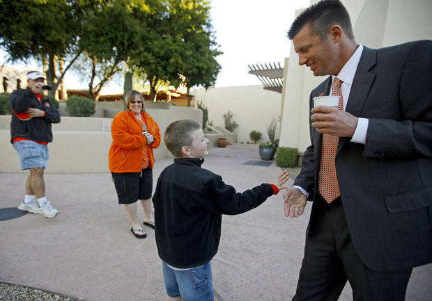 photo - Seven-year-old Michael Bruce, of Canton, Ga., slaps hands with Oklahoma State coach Mike Gundy as his parents Jeremy and Courtney Bruce watch after a Fiesta Bowl press conference in January. Gundy and his players have been showered with appreciation by fans since winning their first Big 12 Conference title and BCS bowl. Photo by Bryan Terry, The Oklahoman.