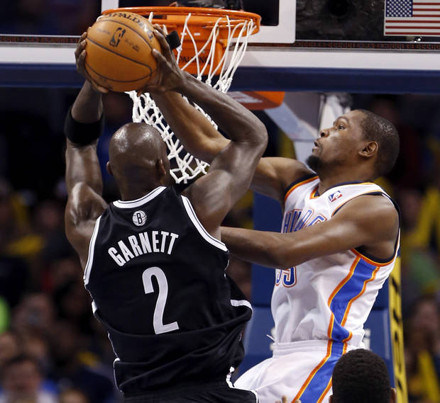photo - Thunder's Kevin Durant (35) blocks a shot by Brooklyn's Kevin Garnett in an NBA basketball game where the Oklahoma City Thunder were defeated 95-93 by the Brooklyn Nets at the Chesapeake Energy Arena in Oklahoma City, on Thursday, Jan. 2, 2014. Photo by Steve Sisney, The Oklahoman
