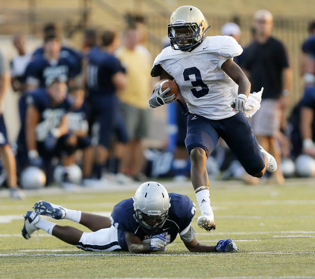 photo - Southmoore's Jaelon Walker (3) breaks away from Enid's Marshawn Mills (21) during a high school football scrimmage at Moore Stadium in Moore, Okla., Friday, Aug. 17, 2012. Photo by Nate Billings, The Oklahoman