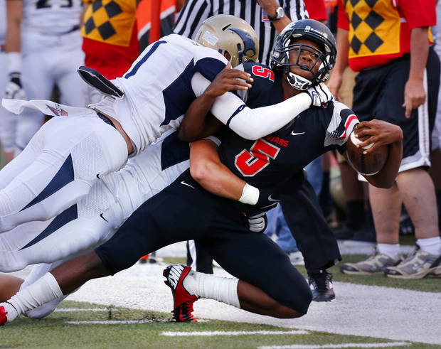 photo - Westmoore Jaguars' quarterback Jhames West is pushed out short of the marker on a fourth down play by Gilbert Reese and Nick Ward as the Southmoore Sabercats play the Westmoore Jaguars in high school football on Friday, Sept. 7, 2012, in Moore, Okla.  Photo by Steve Sisney, The Oklahoman