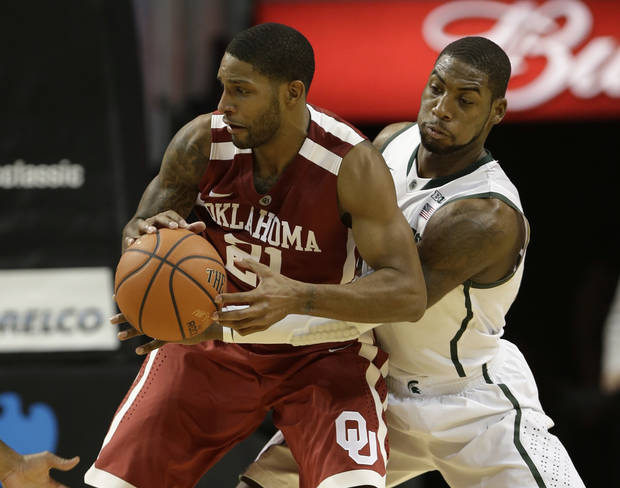photo - Michigan State's Branden Dawson, right, defends against Oklahoma's Cameron Clark (21) during the first half of the championship game in the Coaches vs. Cancer NCAA college basketball game on Saturday, Nov. 23, 2013, in New York. (AP Photo/Frank Franklin II)
