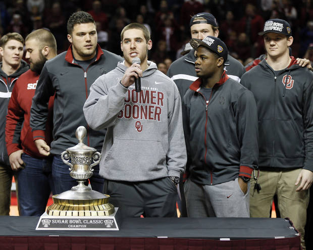 photo - Surrounded by his teammates, OU quarterback Trevor Knight addresses the crowd at halftime of a Sooner basektball game earlier this season.                    Photo by Nate Billings, The Oklahoman