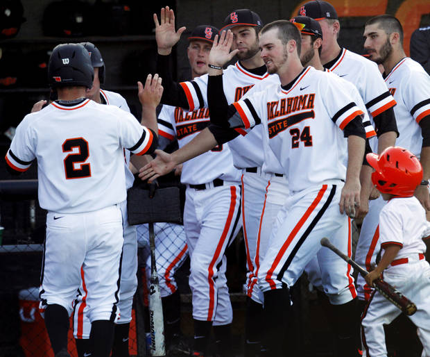 photo - The Oklahoma State bench congratulates Tim Arakawa (2) as he returns from scoring a run during a NCAA college baseball game between Oklahoma State University (OSU) and Arizona State University at Allie P. Reynolds stadium in Stillwater, Okla., Friday, May 2, 2014. Photo by KT King, The Oklahoman