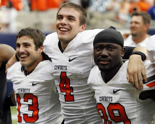 photo - Oklahoma State's J.W. Walsh (4) smiles as he sings the alma mater with David Glidden (13) and Nick Rockwell (89) after the AdvoCare Texas Kickoff college football game between the Oklahoma State University Cowboys (OSU) and the Mississippi State University Bulldogs (MSU) at Reliant Stadium in Houston, Saturday, Aug. 31, 2013. OSU won, 21-3. Photo by Nate Billings, The Oklahoman