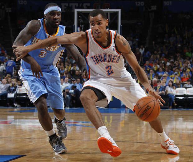 photo - Oklahoma City's Thabo Sefolosha (2) drives the ball past Denver's Ty Lawson (3) during the NBA preseason basketball game between the Oklahoma City Thunder and the Denver Nuggets at the Chesapeake Energy Arena, Sunday, Oct. 21, 2012. Photo by Garett Fisbeck, The Oklahoman