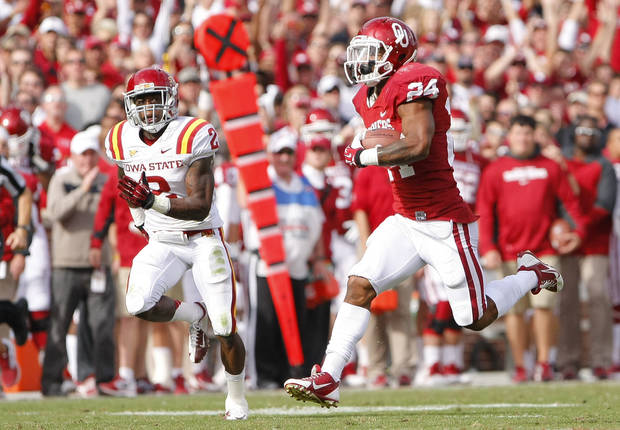 photo - Oklahoma running back Brennan Clay runs past an Iowa State defender in the third quarter of an NCAA college football game in Norman, Okla. on Saturday, Nov. 16, 2013.  Oklahoma won 48-10. (AP Photo/Alonzo Adams)