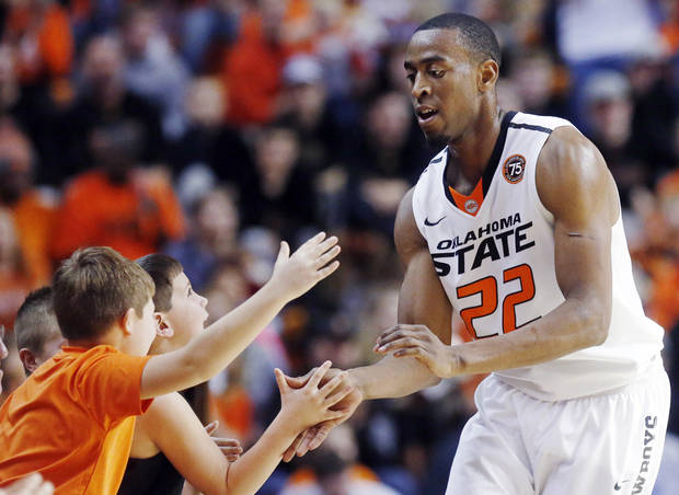 photo - Oklahoma State wing Markel Brown (22) celebrates with fans during the second half of an NCAA college basketball game against Robert Morris in Stillwater, Okla., Monday, Dec. 30, 2013. Oklahoma State won 92-66. (AP Photo/Sue Ogrocki)
