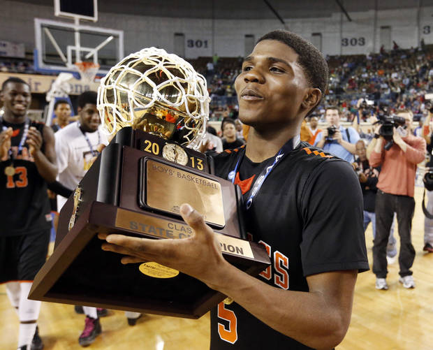 photo - Douglass Stephen Clark carries the championship trophy after his 51 point scoring run during the 4a boys championship game where the Douglass high school Trojans defeated the Roland Rangers 82-80 at the State Fair Arena on Saturday, March 9, 2013 in Oklahoma City, Okla.  Photo by Steve Sisney, The Oklahoman
