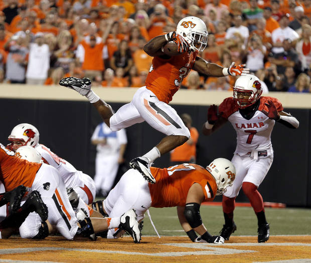 photo - Oklahoma State's Jeremy Smith (31) leaps into the end zone for a touchdown during a college football game between the Oklahoma State University Cowboys (OSU) and the Lamar University Cardinals at Boone Pickens Stadium in Stillwater, Okla., Saturday, Sept. 14, 2013. Photo by Sarah Phipps, The Oklahoman