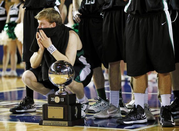photo - Bishop McGuinness' Greg Roberts (10) kneels next to the runner-up silver ball after the Class 5A boys championship high school basketball game in the state tournament at the Mabee Center in Tulsa, Okla., Saturday, March 9, 2013. Tulsa Memorial defeated Bishop McGuinness, 59-42.  Photo by Nate Billings, The Oklahoman