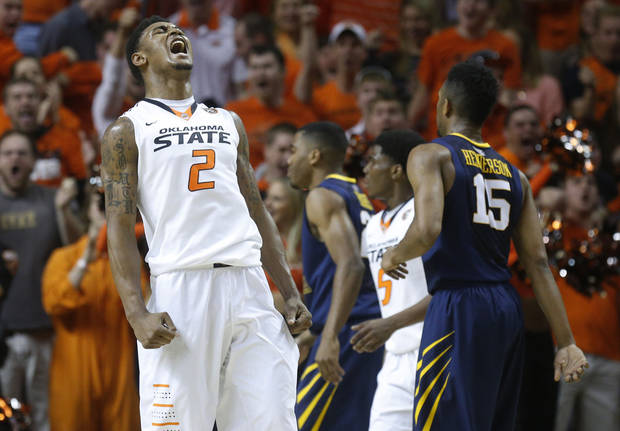 photo - Oklahoma State wing Le'Bryan Nash (2) reacts after dunking near the close of the first half of an NCAA college basketball game against West Virginia in Stillwater, Okla., Saturday, Jan. 25, 2014. West Virginia guard Terry Henderson (15) is at right. (AP Photo/Sue Ogrocki)