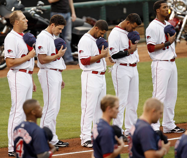 photo - MINOR LEAGUE BASEBALL: Players stand during the national anthem before the 2012 opening day baseball game between the Oklahoma City RedHawks and the Memphis Redbirds at the Chickasaw Bricktown Ballpark in Oklahoma City, Thursday, April 5, 2012. Photo by Nate Billings, The Oklahoman