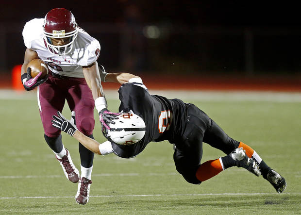 photo - HIGH SCHOOL FOOTBALL: Jordan Smallwood of Jenks pushes down Putnam City's Scott Barker during their high school game at Putnam City in Warr Acres, Okla., Thursday, Nov. 1, 2012. Photo by Bryan Terry, The Oklahoman