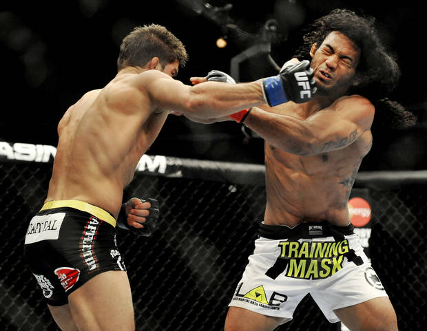photo - Josh Thomson, left, punches Benson Henderson right, during the main event of a UFC mixed martial arts event in Chicago, Saturday, Jan. 25, 2014. (AP Photo/Paul Beaty)
