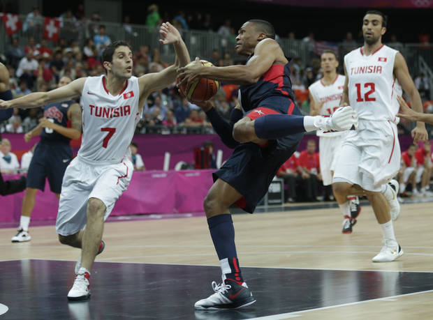 photo - USA's Russell Westbrook, center, drives to the basket against Tunisia's Mourad El Mabrouk, left, during a men's basketball game at the 2012 Summer Olympics, Tuesday, July 31, 2012, in London. (AP Photo/Charles Krupa) ORG XMIT: OBKO171