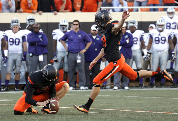 photo - Oklahoma State's Ben Grogan (19) kicks s field goal late in the fourth quarter as Oklahoma State's Michael Reichenstein (59) holds during the second half of a college football game between the Oklahoma State University Cowboys (OSU) and the Kansas State University Wildcats (KSU) at Boone Pickens Stadium in Stillwater, Okla., Saturday, Oct. 5, 2013. OSU won 33-29.Photo by Sarah Phipps, The Oklahoman