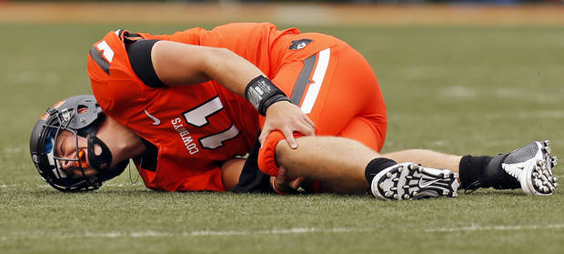 photo - OSU quarterback Wes Lunt (11) holds his knee after being injured on a play in the first quarter during a college football game between Oklahoma State University and the University of Louisiana-Lafayette (ULL) at Boone Pickens Stadium in Stillwater, Okla., Saturday, Sept. 15, 2012. Lunt left the bench area on crutches in the first quarter. Photo by Nate Billings, The Oklahoman