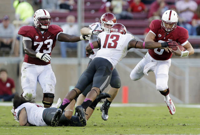 Stanford quarterback Josh Nunes (6), right, leaps next to Washington State linebacker Darryl Monroe (13) during the second half of an NCAA college football game in Stanford, Calif., Saturday, Oct. 27, 2012. Stanford won 24-17. (AP Photo/Marcio Jose Sanchez)