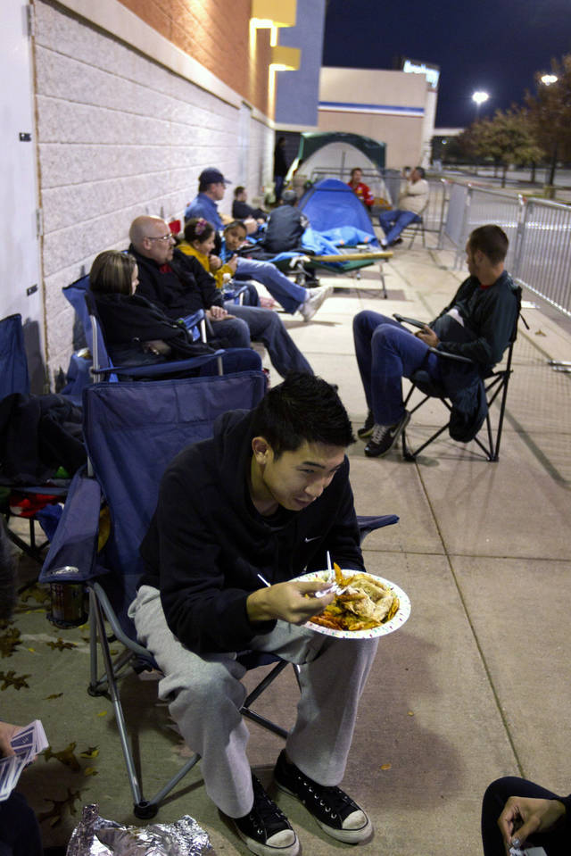Khang Nguyen, of Arlington, Texas eats his Thanksgiving dinner while waiting in line at a Best Buy store in Grapevine, Texas on Thursday, Nov. 22, 2012. Despite a surge of resistance as the sales drew near, with scolding editorials and protests by retail employees and reminders of frantic tramplings past, Black Friday's grip on America may be stronger than ever. (AP Photo/Star-Telegram/Joyce Marshall)