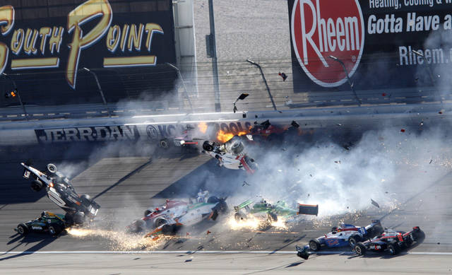 Drivers, including Dan Wheldon (77, in air at left), crash during a wreck that involved 15 cars during the IndyCar Series' auto race at Las Vegas Motor Speedway in Las Vegas on Sunday, Oct. 16, 2011. Wheldon died following the crash. (AP Photo/Las Vegas Review-Journal, Jessica Ebelhar) LAS VEGAS SUN OUT MANDATORY CREDIT NO SALES