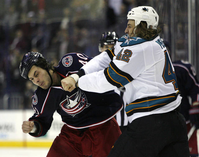 Columbus Blue Jackets' Jared Boll, left, and San Jose Sharks' Matt Pelech (42) fight during the first period of an NHL hockey game, Monday, Feb. 11, 2013, in Columbus, Ohio. Boll set a team record of 120 fights. (AP Photo/Mike Munden)