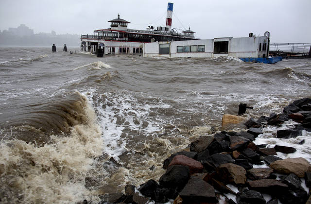 An historic ferry boat named the Binghamton is swamped by the waves on the Hudson River in Edgewater, N.J., Monday, Oct. 29, 2012 as Hurricane Sandy lashed the East Coast. As it drew near, Sandy moved closer to converging with two cold-weather systems to form a superstorm of snow, rain and wind. Forecasters warned of 20-foot waves bashing into the Chicago lakefront and up to 3 feet of snow in West Virginia. (AP Photo/Craig Ruttle) ORG XMIT: NJCR109