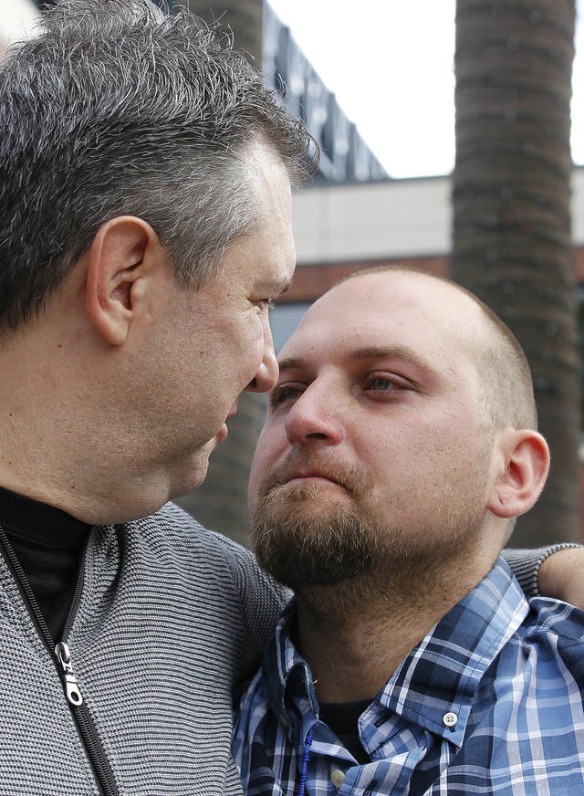 Robert Preece, left, and Robert Preece Jr., father and brother of Los Angeles Dodgers fan Jonathan Denver, embrace during a public plea for witnesses to Wednesday's fatal stabbing of Denver, during a news conference outside AT&T Park before the Giants' baseball game in San Francisco, Sunday, Sept. 29, 2013. (AP Photo/Tony Avelar)