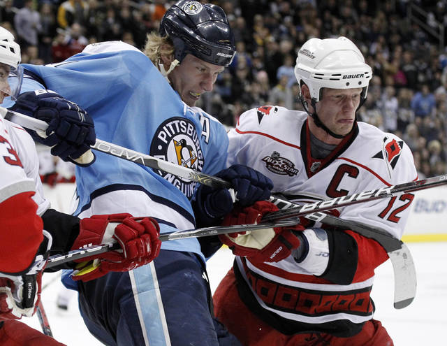 FILE - In this Jan. 22, 2011, file photo, Pittsburgh Penguins' Jordan Staal, left, and his brother Carolina Hurricanes' Eric Staal (12) battle in the corner during the third period of an NHL hockey game in Pittsburgh. Staal said Saturday that he was midway through his wedding reception when he found out the Pittsburgh Penguins traded him to his big brother's team — the Hurricanes. (AP Photo/Gene J. Puskar, File)
