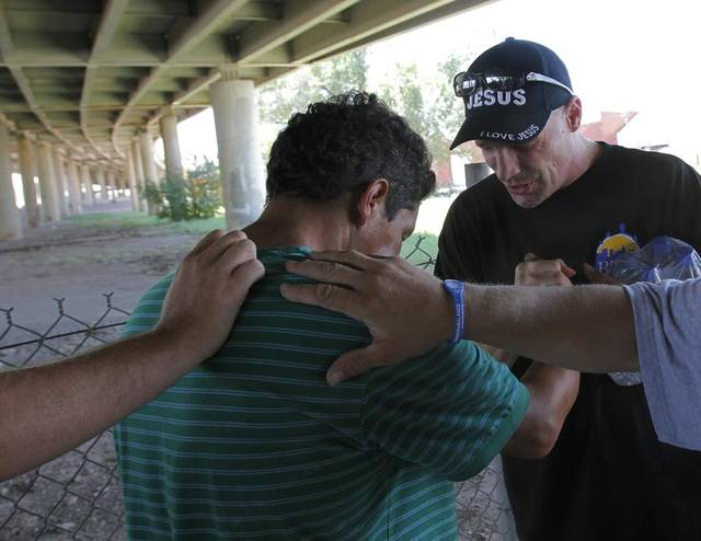 HEAT / SUMMER / HOT WEATHER / RELIEF / ASSISTANCE / AID: Scott Sanchez prays over Manuel Garcia, a homeless man, after providing him with water from the City Rescue Mission in Oklahoma City Friday, Aug. 5, 2011.  Photo by Garett Fisbeck, The Oklahoman ORG XMIT: KOD