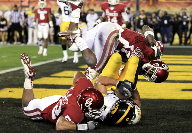 Iowa's C.J. Fiedorowicz, bottom right, scores a touchdown between Oklahoma's Kellen Jones, left, and Tony Jefferson, top, in the fourth quarter in the Insight Bowl NCAA college football game Friday, Dec. 30, 2011, in Tempe, Ariz. Oklahoma defeated Iowa 31-14.(AP Photo/Ross D. Franklin)
