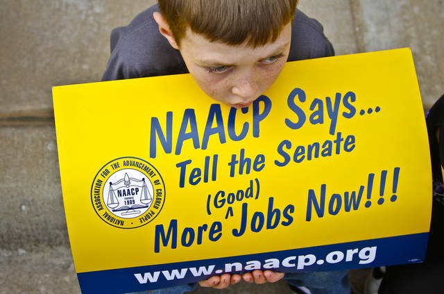 Bret Sears, 9, holds an NAACP sign as he watches the Martin Luther King Jr. Day parade pass through downtown Oklahoma City on Monday, Jan. 16, 2012, in Oklahoma City, Okla. Photo by Chris Landsberger, The Oklahoman