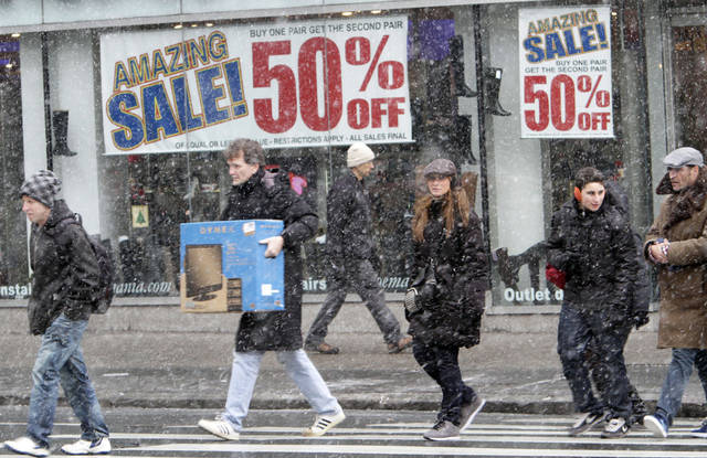 Shoppers make their way in the snow in Union Square in New York. AP FILE PHOTO