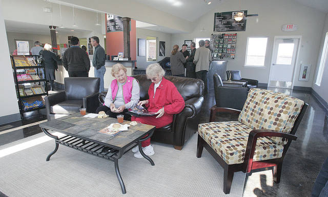 Westwood Tennis Center members Jean Callahan and Gene Harper look over a book of photos in the new lounge.