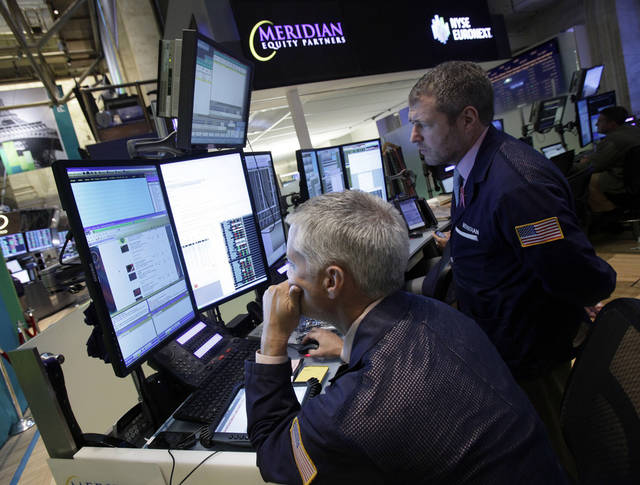 FILE - In this Thursday, Sept. 13, 2012 file photo, a pair of traders work in their booth on the floor of the New York Stock Exchange. Hopes that the U.S. is back in recovery mode has helped stocks start the new month on a relative high. (AP Photo/Richard Drew, File)