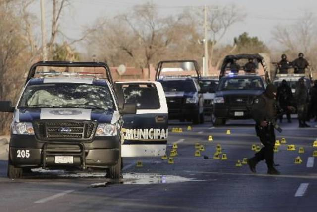 A Mexican soldier walks near a bullet-riddled police vehicle at the scene where three police officers were killed in Ciudad Juarez, northern  Mexico, Tuesday, Feb. 17, 2009. The three officers, including the director of operations of the city's Public  Safety Department, were shot to death by unidentified gunmen on a street near the U.S. consulate. (AP Photo/Eduardo Verdugo)